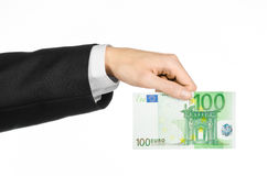 Money and business topic: hand in a black suit holding a banknote 100 euro isolated on a white background in studio. Money and business topic: hand in a black Royalty Free Stock Image