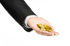Money and business topic: hand in a black suit holding a pile of gold coins in the studio on a white background isolated. Money and business topic: hand in a Royalty Free Stock Photo