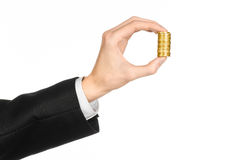 Money and business topic: hand in a black suit holding a pile of gold coins in the studio on a white background isolated. Money and business topic: hand in a Stock Photo