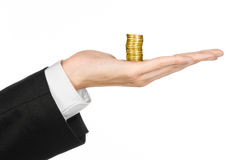 Money and business topic: hand in a black suit holding a pile of gold coins in the studio on a white background isolated. Money and business topic: hand in a Stock Photos
