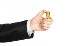 Money and business topic: hand in a black suit holding a pile of gold coins in the studio on a white background isolated. Money and business topic: hand in a Stock Photography
