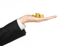 Money and business topic: hand in a black suit holding a pile of gold coins in the studio on a white background isolated. Money and business topic: hand in a Stock Image