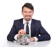 Money. Businessman putting a coin into a piggy bank isolated on white background Royalty Free Stock Photos