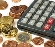 Money calculations. Several euro coins and one calculator stock photo