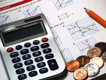 Money, Calculations and Math. A calculator with money and pencils on a textbook Stock Photo