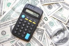 Money and calculator. A pile of dollars and a pocket calculator Royalty Free Stock Photo