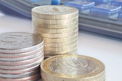 Money and calculator. Three piles of coins on the background of a pocket calculator Stock Image