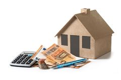 Money and calculator in front of a house model from cardboard, f Stock Image