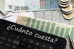 Money, calculator with How much? text in Spanish royalty free stock image