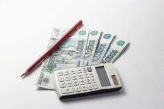 Money with a calculator lying on a white background royalty free stock image