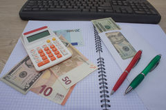 Money with calculator and notebook computer on wood table Royalty Free Stock Photos