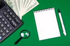 Money, calculator and notebook on green background royalty free stock images