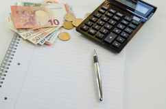 Money, calculator and pen Stock Photos