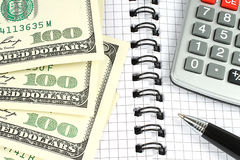 Money, calculator, and pen on notepad Royalty Free Stock Images