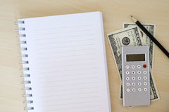 Money, calculator, pencil and blank notebook on wood background, Royalty Free Stock Images