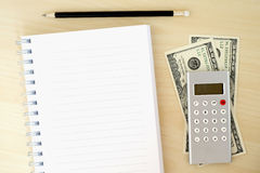 Money, calculator, pencil and blank notebook on wood table, busi Royalty Free Stock Images