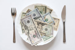 Money can not be eaten. U.S. dollars on a plate with knife and fork Royalty Free Stock Photography