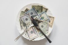 Money can not be eaten. U.S. dollars on a plate with knife and fork Royalty Free Stock Images