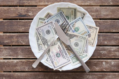 Money can not be eaten. U.S. dollars on a plate with knife and fork Royalty Free Stock Photo