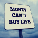 Money can't buy life. Idiom Money can't buy life written on white billboard, retro effect faded look Stock Photo