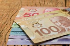 Money from Canada: Canadian Dollars. Close up of cash bills on r. Ustic wood table royalty free stock images