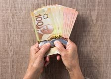 Money from Canada: Canadian Dollars. Overhead of senior person h. Olding bills royalty free stock photography