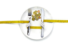 MONEY CANNOT BE EATEN. A fork & knife wrapped with a measure, and placed on a dish that has money inside instead of food Royalty Free Stock Images