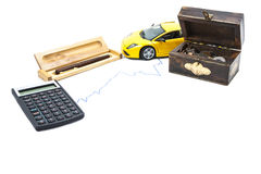 Money, car, calculator and pen. A treasure box with money, a car, a calculator and a pen Stock Image