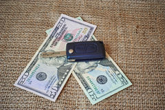 Money and car keys on a burlap Royalty Free Stock Photo