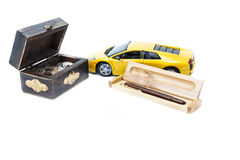 Money, car and pen. A treasure box with money, a car and a pen Royalty Free Stock Photography