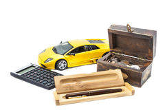 Money, car and pen. A treasure box with money, a car, a calculator and a pen Stock Images