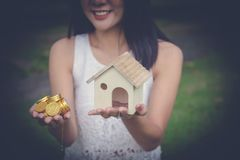 Money cash and a model home in woman hands. stock photo