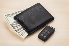 Money cash wallet and car remote key. On wooden table Stock Image