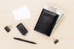 Money cash wallet and car remote key on wooden table Royalty Free Stock Image