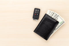Money cash wallet and car remote key on wooden table Stock Photography