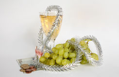 Money and champagne. Money and champagne grapes - a still-life on white Royalty Free Stock Photos
