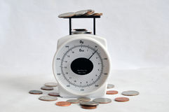 Money and change on a weight scale Royalty Free Stock Photo