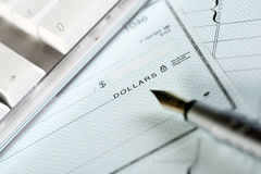 Money check. Pen and keyboard Royalty Free Stock Photography