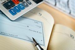 Money check. Pen and calculator Stock Image
