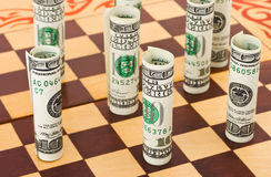 Money on chess board Stock Photos