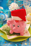 Money for christmas ?. Pink piggy bank in santa hat on christmas table Royalty Free Stock Photo
