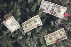 Money on a Christmas-tree. Dollar bills clipped to a Christmas-tree. New Year background. Close up Royalty Free Stock Images
