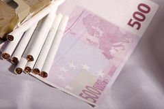 Money and cigarettes Royalty Free Stock Images