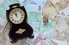 Money, a clock and a house Stock Photography