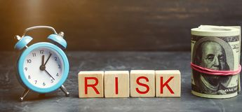 Money, clock and wooden blocks with the word Risk. The concept of financial risk. Justified risks. Investing in a business project royalty free stock photo