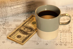 Money and coffee on architectural design Royalty Free Stock Photo