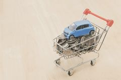 Money coin and car in shopping cart on wood table. auto loan. Concept royalty free stock photos