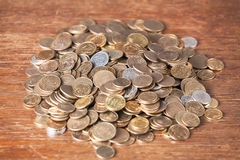 Money coin spare change pile dark wood background. Royalty Free Stock Photo