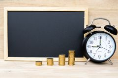 Money coins bar alarm clock and chalkboard on wood table represents a plan for saving money Time management For investment for the royalty free stock images