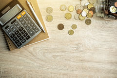 Money coins, calculator and some stationery on wood table Stock Images